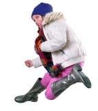 Isolerad höststående av barnet med att hoppa för hatt, för halsduk och för kängor Arkivbild