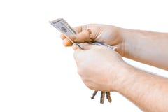 Isolerad hand med kontanta pengardollar och biltangent Vit bakgrund Människan räcker innehavtangenter på a Royaltyfri Bild