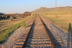 Isolerad järnväg linje med raka järnvägsspår som leder in i avståndet Royaltyfri Bild