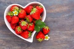 isolerad jordgubbewhite f?r bakgrund hj?rta Nya jordgubbar i platta p? den vita tr?tabellen B?sta sikt, kopieringsutrymme arkivbild