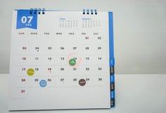 Isolerad Juli kalender med möte-, tidsbeställnings- och räkningbetalning Arkivbild
