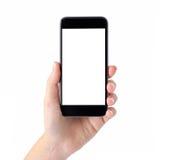 Isolerad kvinnlig hand som rymmer en telefon med den vita skärmen arkivbild