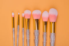 Isolerad pastellfärgad bakgrund för smink borstar Fotografering för Bildbyråer