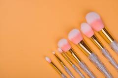 Isolerad pastellfärgad bakgrund för smink borstar Arkivbild