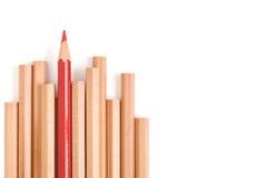 Isolerad röd kulör blyertspennaställning ut ur andra bruna blyertspennor Royaltyfri Foto
