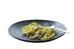 Isolerad spagetti, stekt ost på en svart platta på vita lodisar arkivbild