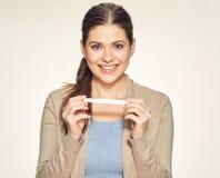 Isolerad stående av att le den unga kvinnan som rymmer det gravida provet arkivfoto