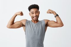 Isolerad stående av den unga gladlynta attraktiva idrotts- mörkhyade mannen med den afro frisyren i sportig grå skjorta royaltyfri fotografi
