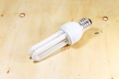 Isolerad standard fluorescerande tubformig lampa på wood bakgrund Arkivfoto
