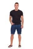 Isolerad stilig tillfällig man i jeanskortslutningar royaltyfri bild