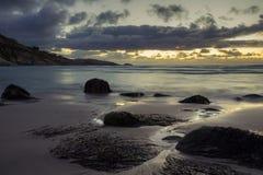 Isolerad strand under en dramatisk solnedgånghimmel Arkivbilder