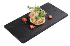 Isolerad tärnad laxsallad med avokadot, tomaten, löken, chili och koriander tjänade som i svart rektangelstenplatta på washi Arkivbilder