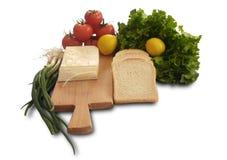 Isolerad tomat, citron, grönsallat, bröd, ny salladlök och ost Royaltyfri Fotografi