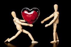Isolerad träfalsk hållande röd hjärta arkivbild