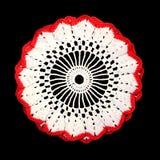 Isolerad virkad dekorativ vit doily med den röda gränsen på en svart bakgrund Rund volymetrisk doily fotografering för bildbyråer