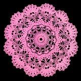 Isolerad virkad rosa doily med en modell av kottar, sidor och bågar på en svart bakgrund Rund dekorativ bomullsdoily royaltyfria bilder