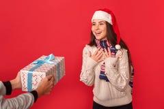 isolerad white för beröm begrepp Persong som ger gåvan till den unga kvinnan i halsduk- och santa hattanseende som isolerades på  royaltyfri fotografi