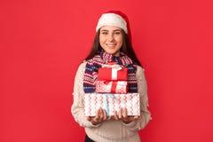 isolerad white för beröm begrepp Ung kvinna i halsduk- och santa hattanseende som isoleras på rött med att le för gåvaaskar som ä royaltyfri fotografi