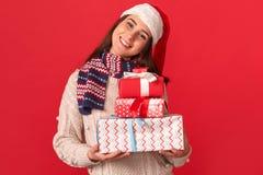 isolerad white för beröm begrepp Ung kvinna i halsduk- och santa hattanseende som isoleras på rött med gåvaaskar som ler glad när royaltyfria bilder