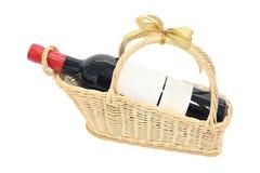 Isolerad wineflaska med den blanka etiketten på korg Royaltyfri Bild