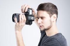 Isolerade den hållande kameran för den unga mannen i svart skjorta studion Royaltyfri Fotografi