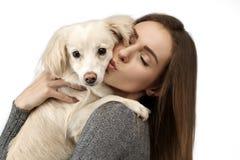 Isolerade den stiliga unga kvinnan för Closeupståenden som kysser hans bra vänhund, bakgrund royaltyfri foto
