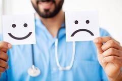 isolerade fängelsekunder för armomsorg hälsa Doktor Holding kort med symbolgyckel och ledsna Smil arkivfoto