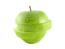 Isolerade gröna äppleskivor med vattendroppar Arkivfoto