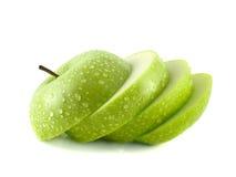 Isolerade gröna äppleskivor med vattendroppar Fotografering för Bildbyråer