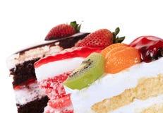 Isolerade jordgubbe, choklad, kiwi och orange fruktkaka Fotografering för Bildbyråer