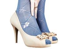 Isolerade kvinnors beigea läderskor med sönderrivet   strumpbyxor Royaltyfria Bilder