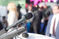 isolerade mikrofoner för bakgrund trycker på konferensen white Arkivfoto
