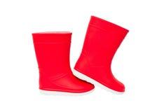 Isolerade röda rainboots Gummistöveler för ungar Fotografering för Bildbyråer