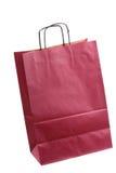 Isolerade shoppingbordeaux, bordeaux-färgade gåvapåsar och äpple Royaltyfria Bilder