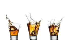 Isolerade skott av whisky med färgstänk på vit Arkivbild