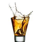 Isolerade skott av whisky med färgstänk på vit Royaltyfri Fotografi