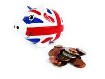 Isolerade Storbritannien spargris- och pengarmynt Fotografering för Bildbyråer