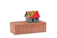 Isolerat begrepp för röd tegelsten och för modellbyggnad för litet hus Royaltyfria Bilder