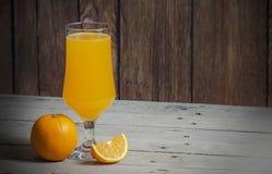 Isolerat och helt exponeringsglas av apelsinen med fruktsaft på trätabellbakgrund Arkivbild