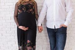 Isolerat på vit Lyckliga gravida parhållhänder av de Gravida familjinnehavhänder Begrepp av union, service och f Fotografering för Bildbyråer