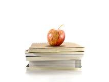 Isolerat rött äpple med böckerna arkivfoton