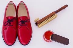 Isolerat rött skor och hjälpmedel på omsorg av skodon Royaltyfria Foton