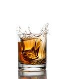 Isolerat skott av whisky med färgstänk på vit Arkivbilder