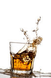 Isolerat skott av whisky med färgstänk på vit Arkivfoton