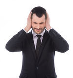 Isoleted on white. Annoyed businessman covering his ears with his hands, closing eyes royalty free stock images