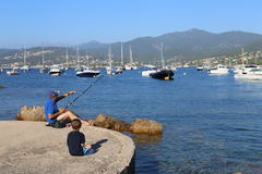 Isoletta, Corsica, France. August 2rd 2016. A fisherman in a small harbor in Corsica with a child learning to fish. Illustration of a family enjoying fishing Royalty Free Stock Images