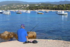 Isoletta, Corsica, France. August 2rd 2016. A fisherman in a small harbor in Corsica. Illustration of a senior enjoying fishing Stock Photo