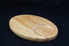 Isolez le plateau en bois ovale vide sur le fond noir, avec le chemin de travail Photographie stock