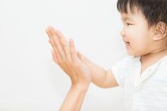 Isoli la mano asiatica sveglia di tocco del bambino con la madre Fotografia Stock