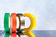 Isolierband von verschiedenen Farben auf einem grauen Hintergrund, Kopienraum stockfoto
